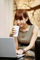 Businesswoman drinking coffee while working on laptop