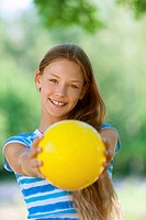 smiling teenage girl holding yellow ball