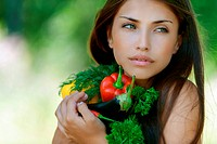 dark-haired sad young woman holding vegetables