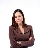 Young women has her arms crossed She is of mixed race Wearing a brown suit and has long brown hair