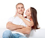 young couple home - woman trying to please her serious boyfriend