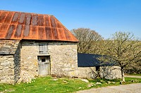 An old barn with a red corrugated iron roof on Dartmoor near Dartmeet, Devon, England