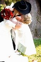 bride & cowboy / groom embraced in a passionate kiss on their wedding day