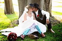 rodeo cowboy kissing his new wife wearing blue cowboy boots sitting together in a grove of trees in a private moment before the party