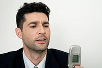 Mid-adult businessman looking at cell phone, frowning