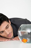 Businessman looking at goldfish in fishbowl