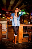 Portrait of a young women inside a bar having fun.