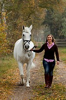 Hanoverian Horse. Young woman leading grey mare