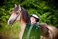 Frederiksborger. Rider in historic costume standing next to a dun stallion