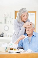 Older woman feeling sick husband's forehead