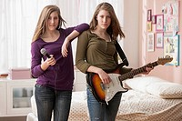 Caucasian girls playing music in bedroom