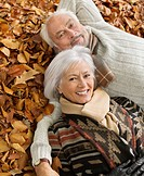 Older couple laying in autumn leaves