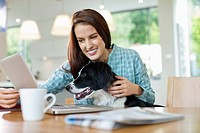Woman with dog on lap using laptop