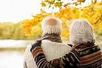 Older couple hugging in park