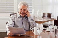 Hispanic businessman reading papers in cafe