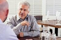 Businessmen talking in cafe