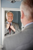 Businessman adjusting his tie in mirror