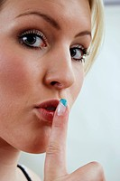 Young woman holding her forefinger to her lips, symbol for silence, hush, silentness
