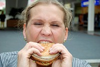 Chubby woman eating hamburger, burger, fast food