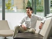 Businessman on sofa in office lobby