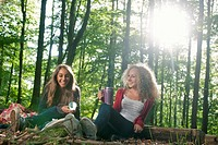 Teenage girls having picnic in forest
