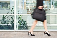 Businesswoman walking on city street