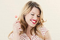 Smiling woman eating lollipop