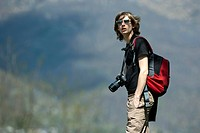 Teenage boy hiking with camera