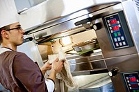 Baker putting food in oven in kitchen