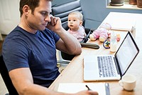 Baby girl sitting with father at work