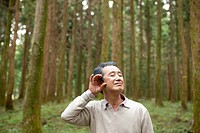 middle aged man listening nature in forest