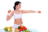 Woman with dumbbells in front of table full of fruit