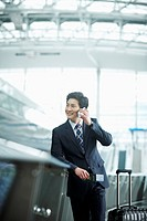 a businessman making a call while holding a passport