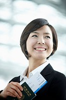 close up shot of a businesswoman smiling holding a boarding pass and passport