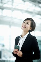 close up shot of a businesswoman smiling holding a passport
