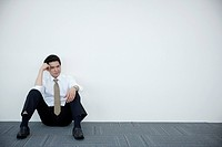 a distressed businessman sitting against wall