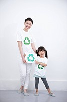 mother and daughter holding recycling symbol board