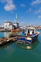 England, Hampshire, Portsmouth, View of fishing boats in harbour and Spinnaker Tower in background
