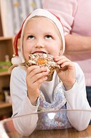 Germany, Girl eating gingerbread, looking up