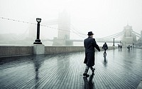 Man walking along Thames path towards Toward Bridge in a foggy rainy day, London, UK