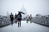 Woman with a umbrella crossing Millennium bridge in a rainy day towards St. Paul's Cathedral