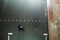 Policeman crossing street, viewed from above, Canary Wharf, London, UK