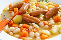 Bowl of bean soup with carrots, potatoes and mini sausages, close up