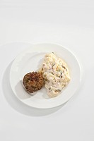 Plate of potato salad with meatball on white background