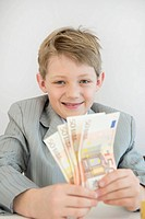 Boy holding Euro notes, smiling