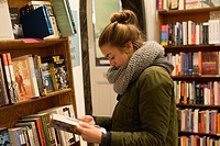 Teenage girl, 17, in City Lights Bookstore, North Beach, San Francisco, California, USA.