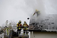 Firefighters wearing breathing equipment while extinguishing a roof fire, removing the roof tiles to access the roof, Aichwald, Baden-Wurttemberg, Ger...