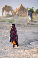 Indian girl walk in the desert early morning