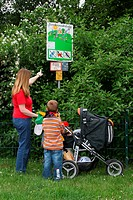 mother explaining an information sign at playground to her son , Germany, North Rhine-Westphalia