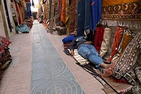 Man Sleeping On A Carpet Outside His Shop In The Carpet Market In Essaouira, Morocco
